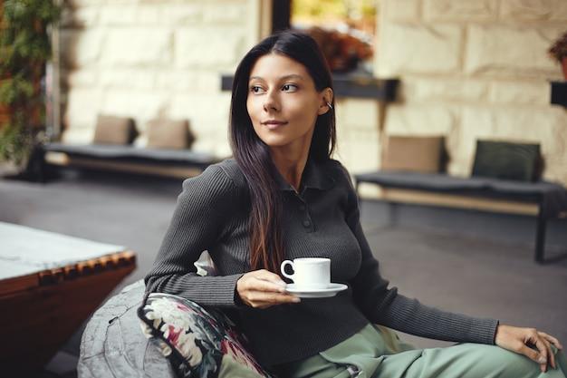 Очаровательная девушка с чашкой кофе сидит в летнем кафе и смотрит в сторону