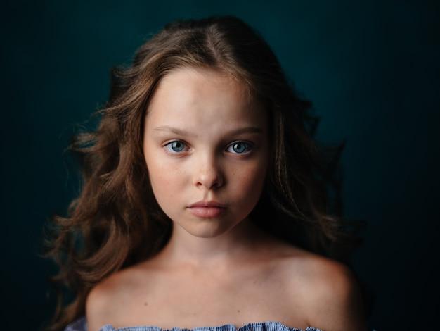 Очаровательная девушка с вьющимися волосами с обнаженными плечами в синем сарафане на темном фоне