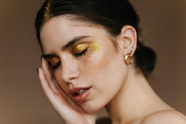 目を閉じてポーズをとるエレガントなイヤリングを持つ愛らしい女の子。ゴージャスなブルネットの女性のクローズアップの肖像画。