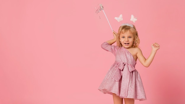 Adorable girl with fairy costume with want and copy space