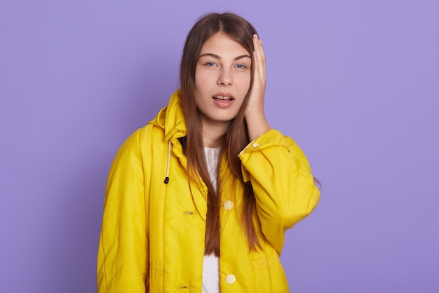 頭に手を持っている愛らしい女の子、重要な何かを忘れて、黄色のジャケットを着て、口を開けてカメラを見て、間違いを犯し、薄紫色の背景の上に孤立してポーズをとる。