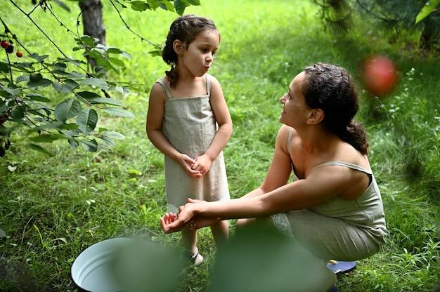 庭で摘みながらさくらんぼを食べる魅力的な母親と一緒に愛らしい女の子。幸せな母性と子供時代、愛、優しさ。一緒に時間を楽しんでいます。幸せな家族。ポジティブな人間の感情。