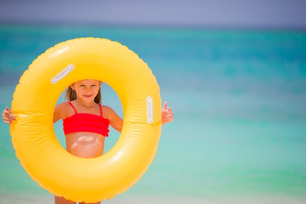 Adorable girl with inflatable rubber circle on white beach