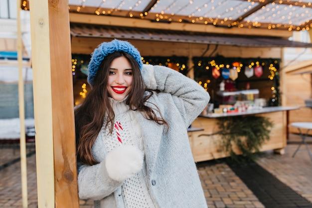 Очаровательная девушка с длинными каштановыми волосами позирует с улыбкой возле рынка, украшенного рождественской гирляндой. открытый портрет радостной европейской леди в модном сером пальто, держащей леденец на палочке и смеясь.