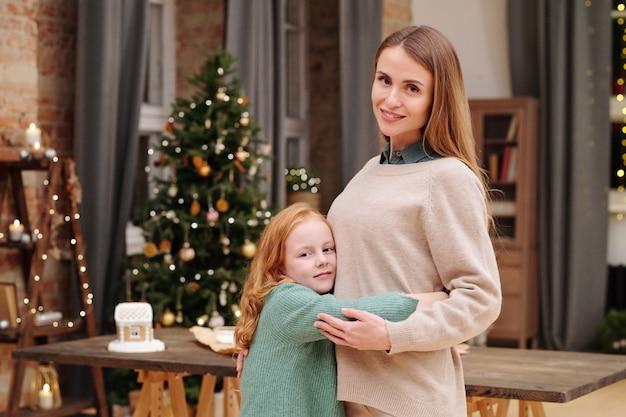 장식 된 firtree에 대해 당신을보고 집에서 촛불을 태우는 동안 그녀의 어머니를 껴안은 긴 생강 머리를 가진 사랑스러운 소녀
