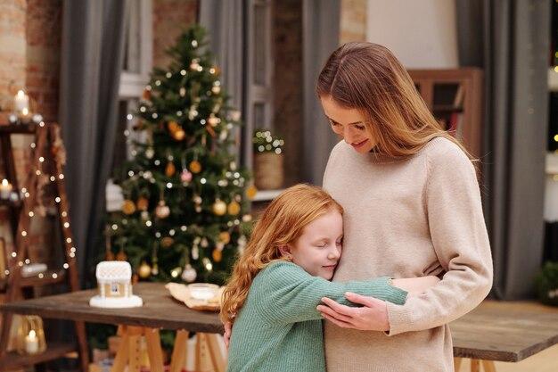긴 물결 모양의 생강 머리가 크리스마스 이브에 장식 된 firtree와 불타는 촛불에 대한 카메라 앞에서 그녀의 어머니에게 포옹을주는 사랑스러운 소녀