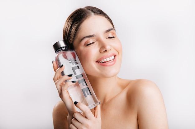 孤立した壁に水のボトルでポーズをとって化粧なしの愛らしい女の子。笑顔のモデルは、生命にとっての水の重要性を示しています。