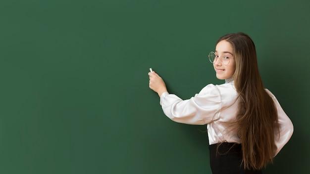 Adorable girl writing on blackboard