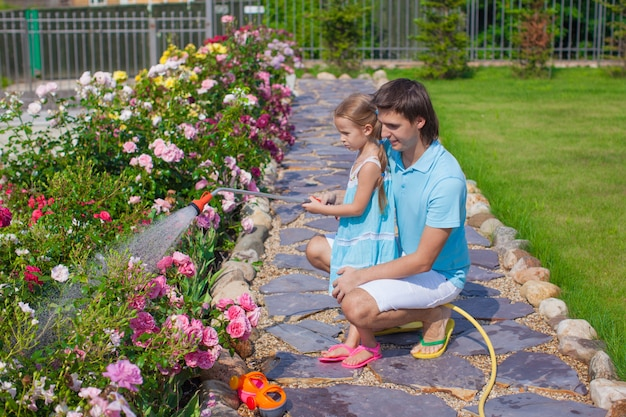 Adorable girl and young father watering flowers with hose in their garden