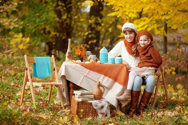Очаровательные девушки проводят чаепитие на улице в осеннем саду