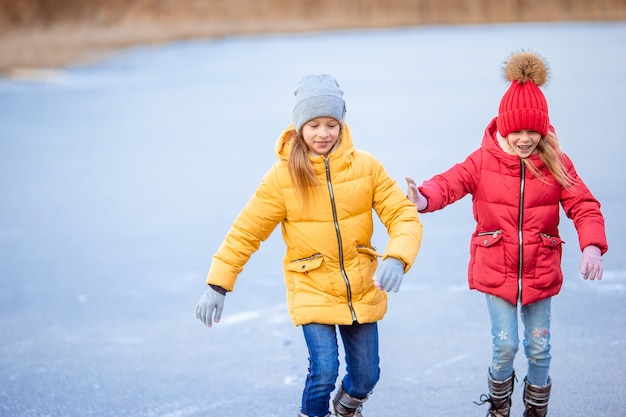 Adorable girls skating on ice rink outdoors in winter snow day