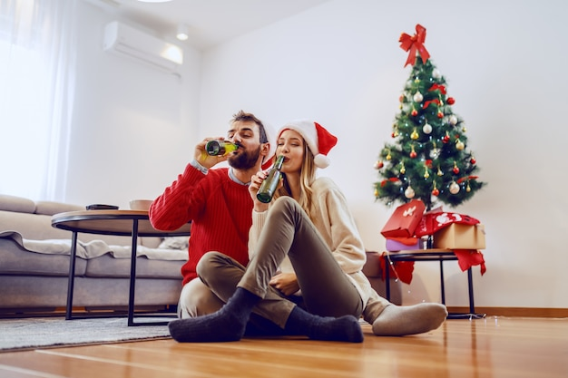 Adorable good-looking caucasian couple with santa hats on heads sitting on floor in living room and drinking beer. in background is christmas tree with presents.