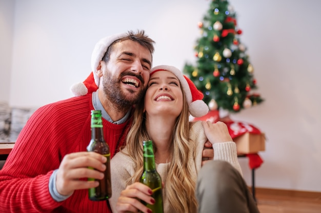 Adorable good-looking caucasian couple with santa hats on heads sitting on floor in living room, hugging and holding beer. in background is christmas tree with presents.