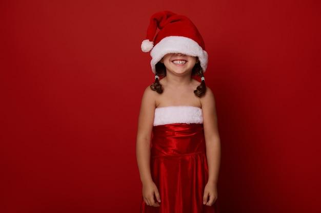 Очаровательная великолепная 4-летняя маленькая девочка, милый ребенок в одежде санта-клауса и шляпе, закрывающей глаза, улыбается зубастой улыбкой, позирует на красном фоне с копией пространства для рождественской и новогодней рекламы