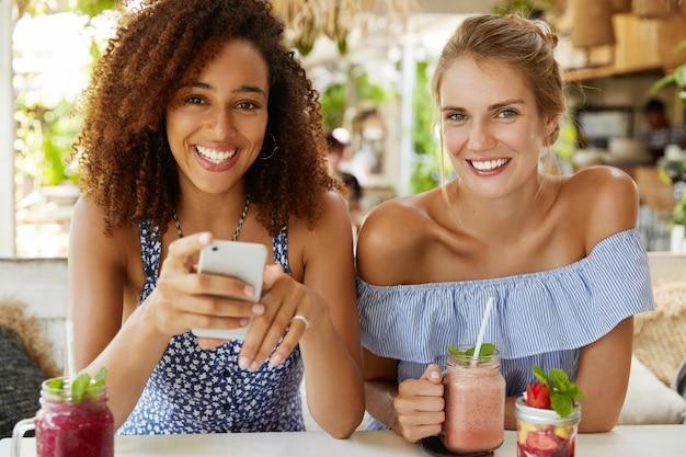 사랑스럽고 화려한 어두운 피부의 여성은 덥수룩 한 헤어 스타일을 가지고 있으며 온라인 커뮤니케이션을 위해 스마트 폰을 사용하여 친한 친구와 만나고, 이국적인 신선한 여름 칵테일로 카페테리아에서 재현합니다. 레저 컨셉