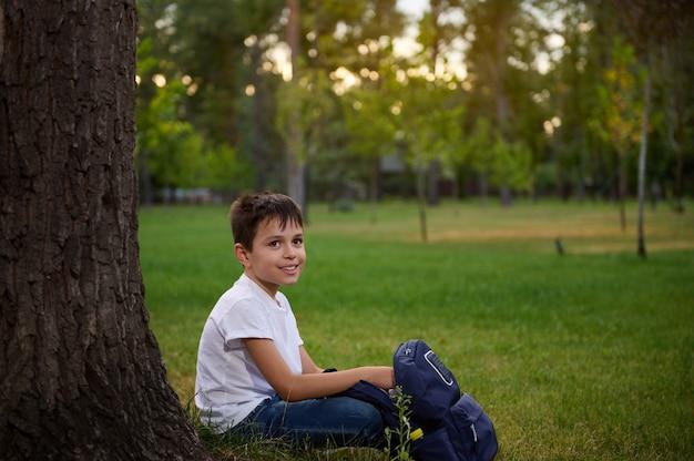 公園で緑の芝生の上に座って、放課後のレクリエーションを楽しんで休んでいる愛らしいハンサムな子供の学校の男の子。バックパックと幸せな賢い小学生の子供の男の子の学生の肖像画。学校に戻る