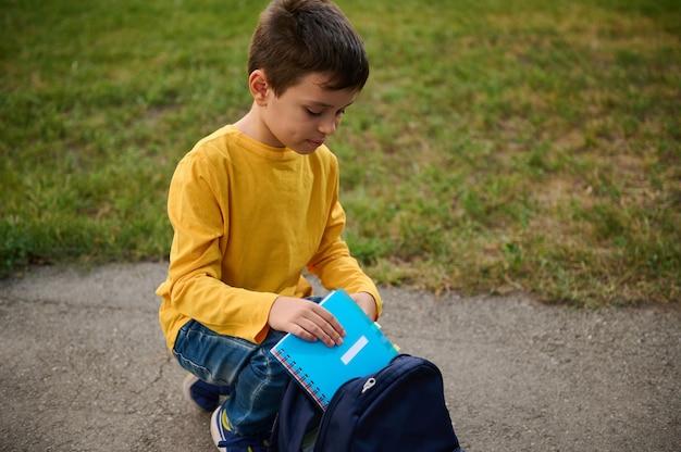 愛らしいハンサムな小学生の男子生徒が公園の小道にひざまずいて、ノートと筆箱をバックパックに入れ、撮影後に帰宅します。学校に戻るコンセプト