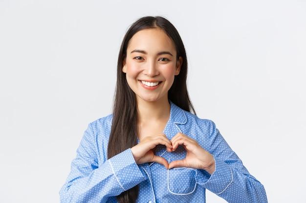 Adorabile ragazza asiatica felice in pigiama blu ama stare a casa, indossare pigiami accoglienti, mostrare il gesto del cuore e sorridere felice, in piedi sfondo bianco ottimista.