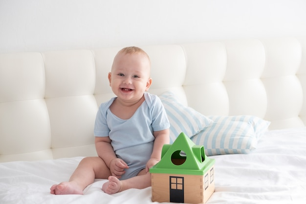 Adorable happy baby boy sits on bed and play with a toy sorter.