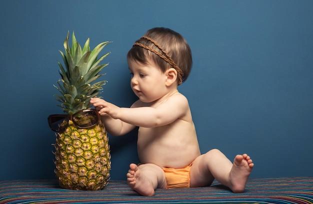 파란색 배경에 파인애플을 가지고 노는 사랑스러운 행복한 아기 소녀