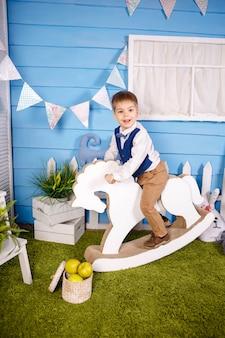 Очаровательный счастливый белокурый маленький мальчик празднует свой день рождения