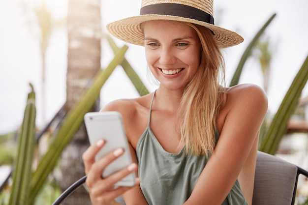 Adorable happy blonde woman dressed casually, wears straw hat and casual t shirt, glad to read good comments under her photo or recieves pleasant message from boyfriend while has summer vacation