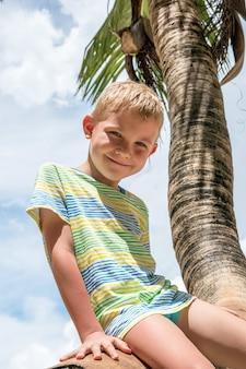ヤシの木の海のビーチに座っている愛らしい幸せな少年
