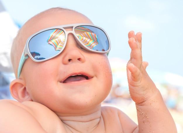 Прелестный счастливый смешной улыбающийся милый мальчик на пляже
