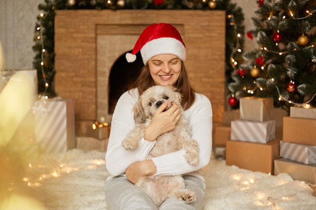 Adorable happy girl in red hat hugging with cute pekingese dog by christmas tree with lights, fireplace and gift boxes in festive room, female sits on floor and having fun with puppy.