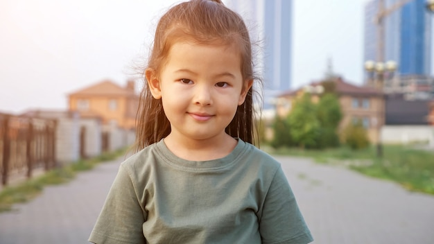 Adorable happy little asian girl in green t-shirt poses for camera standing on city waterfront against buildings in summer evening close view, sunlight