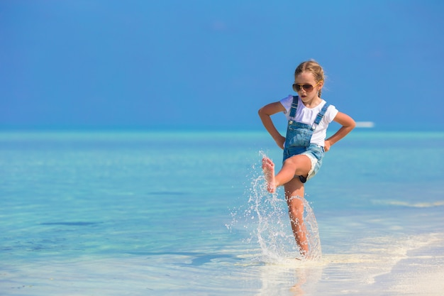 Adorable happy little girl have fun at shallow water on beach vacation
