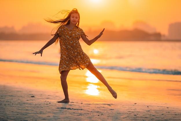 Прелестная счастливая маленькая девочка на белом пляже на заходе солнца.