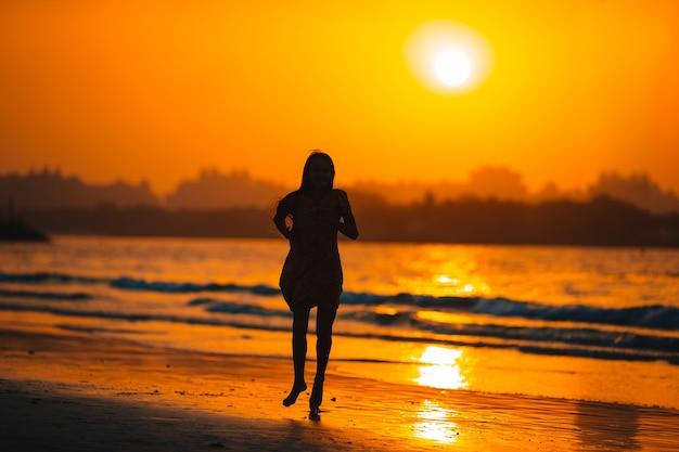 Прелестная счастливая маленькая девочка на белом пляже на закате.