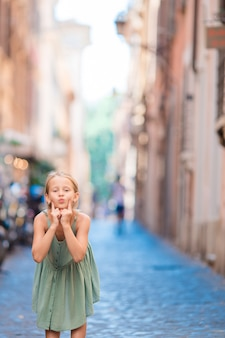 Adorable happy little girl outdoors in european city.