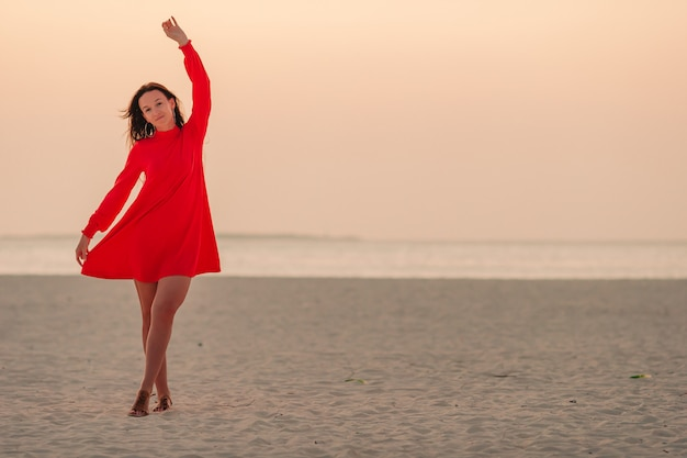 Adorable happy little girl on white beach at sunset.