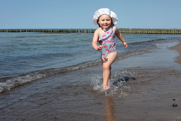 Adorable happy smiling little girl on beach vacation, running along coastline