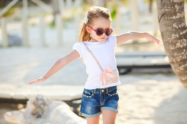 Adorable happy smiling little girl on beach vacation walks squaring arm