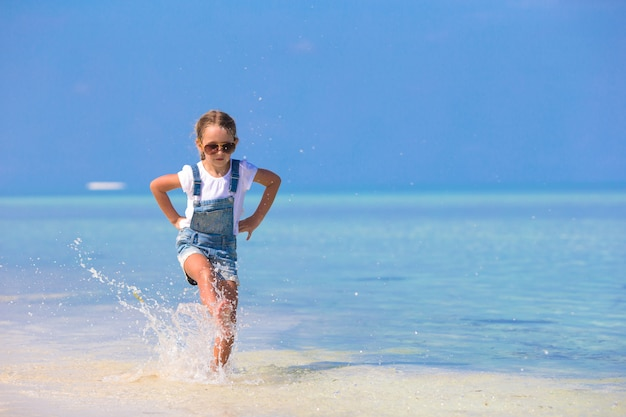 Adorable happy smiling little girl have fun on beach vacation
