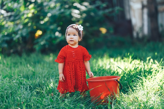Adorable happy toddler girl with knitten flower crown wearing a red dress enjoying picnic in a beautiful blooming fruit garden