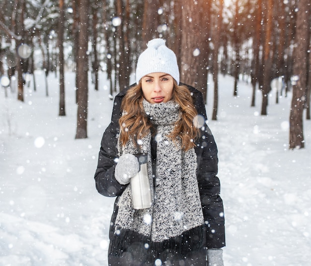 Adorable happy young blonde woman in white knitted hat scarf having fun