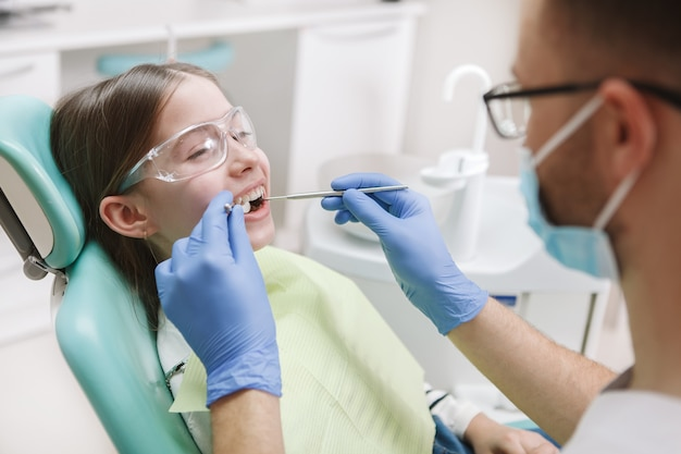Adorable happy young girl smiling at her dentist during teeth treatment