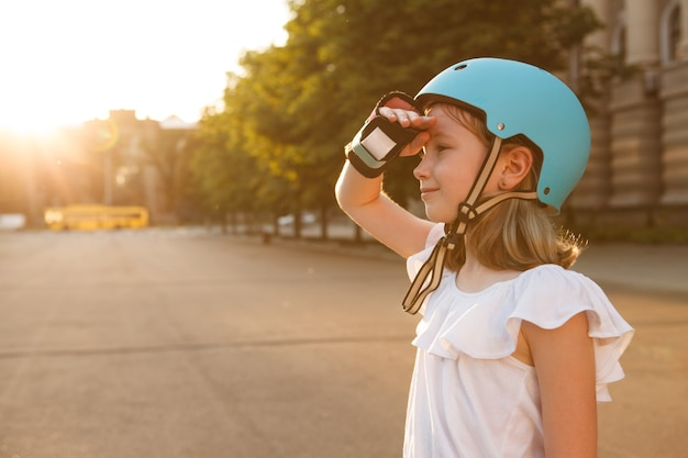 Adorable happy young girl wearing rollerblading helmet and wrist guard looking away joyfully, copy space