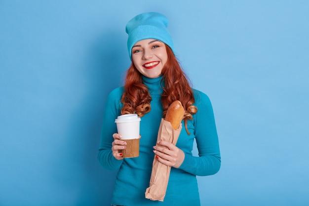 愛らしい幸せな若い女性は行くために長いパンとコーヒーを持っています