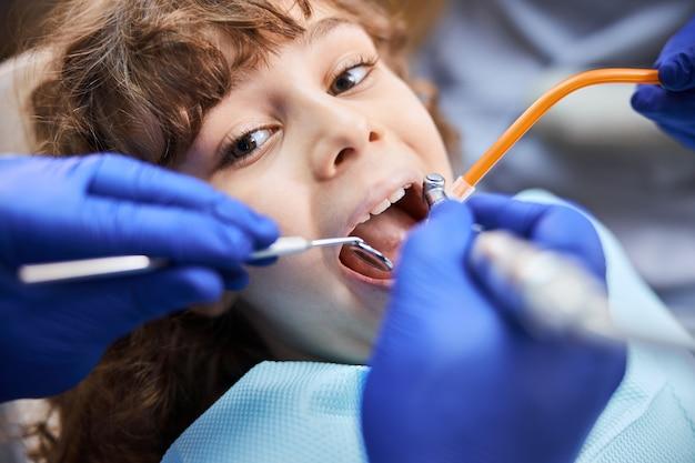 치과 의사 예약 중에 치아를 치료하는 동안 입을 크게 벌리는 사랑스러운 개암 눈의 아이