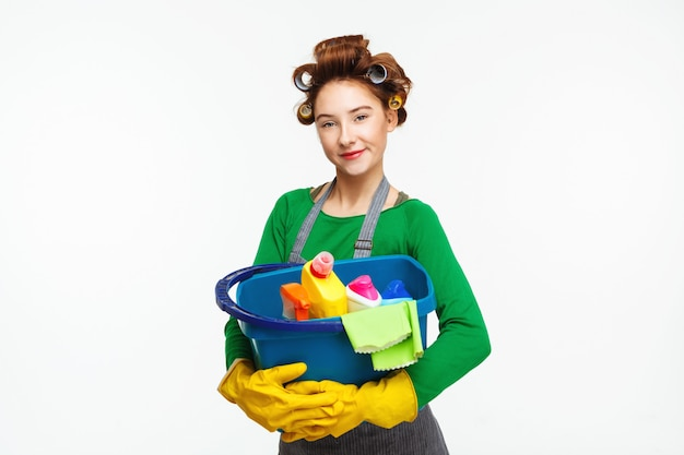 Adorable housewife poses holding cleaning tools wearing yellow gloves