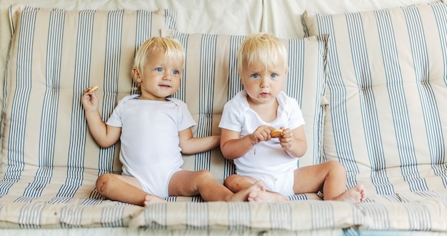 Adorable identical children with light hear and sky blue eyes. toddler twins in white baby's suits sit on a comfortable beige couch in the living room in the morning. family happy moment siblings love
