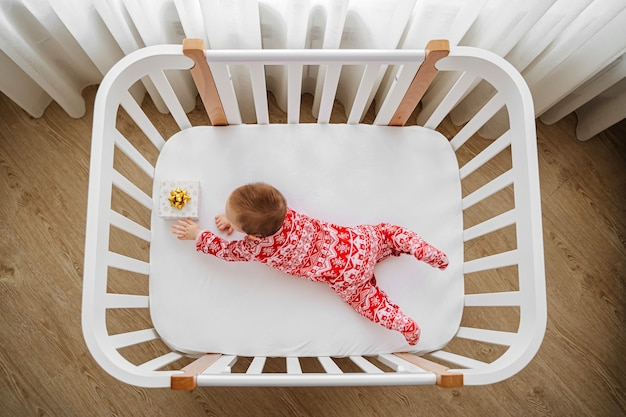 Adorable infant in  christmas pajama with gifts lying  in  cot at home. baby with christmas gifts in cradle in baby's room