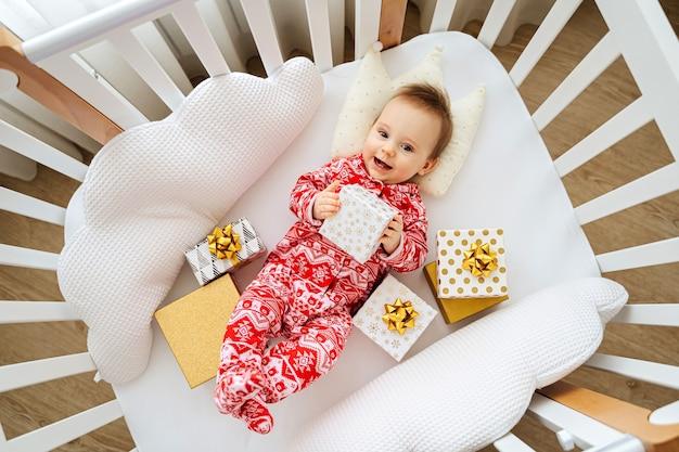 自宅のベビーベッドに横たわっている贈り物とクリスマスパジャマの愛らしい幼児。赤ちゃんの部屋のゆりかごでクリスマスプレゼントと赤ちゃん