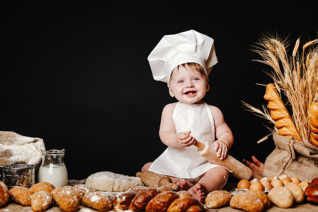 Adorable infant on table with dough
