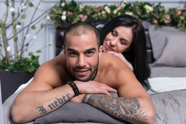 Adorable international couple of man with bare chest and with tattooed hands, brunette woman lying on him on the gray cozy bed in the bedroom